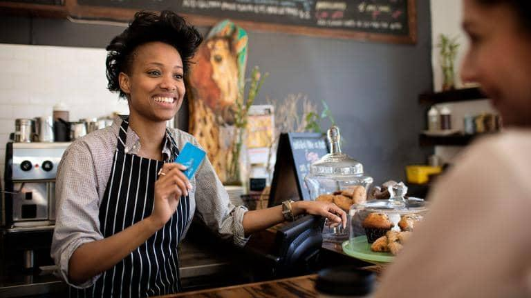 A woman working in a café holds a bank card as she speaks to a customer