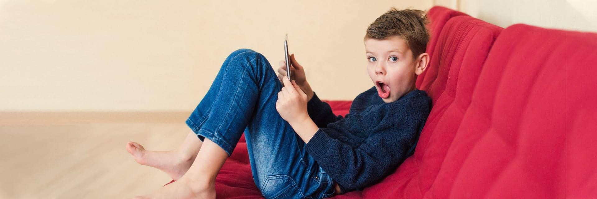 A boy with a look of surprise sits on a red sofa holding a tablet