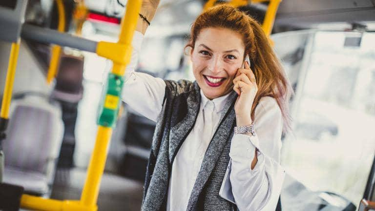 A happy young woman holds a mobile phone to her ear whilst standing in a bus