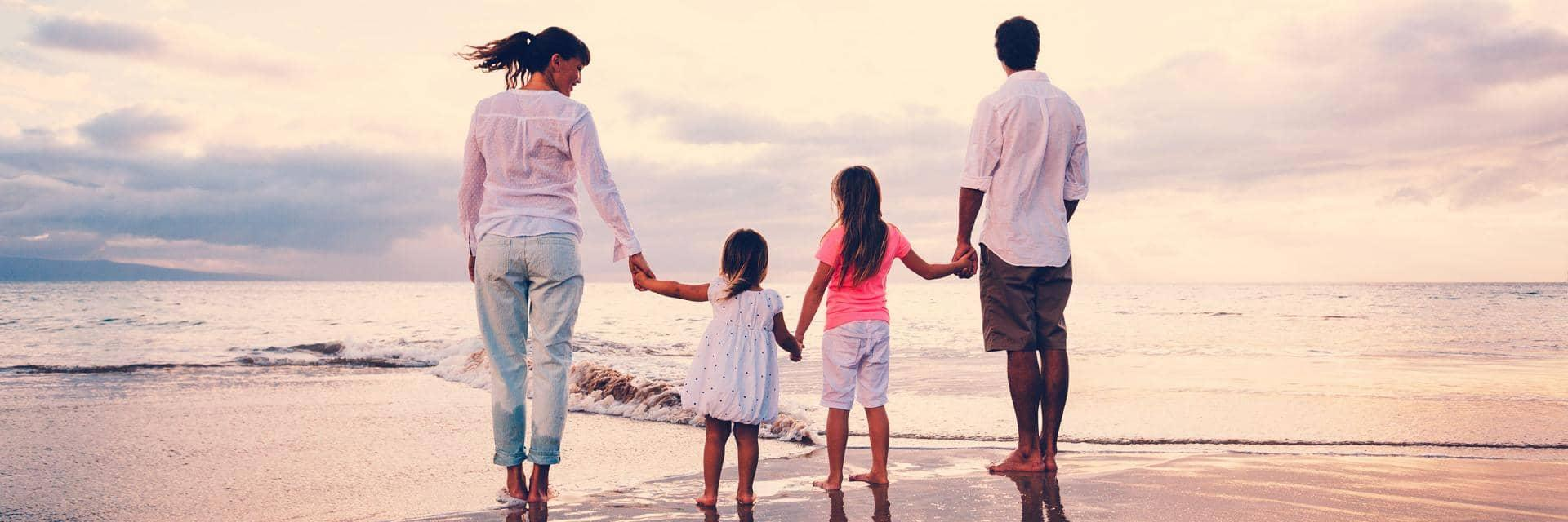 A mum and dad holding the hands of two children on a sandy beach at sunset