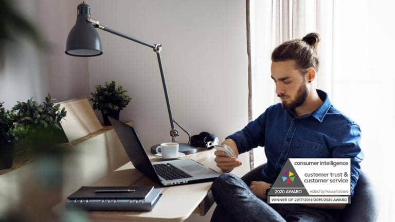 A man sitting at a desk looking at a mobile phone, on the desk is a laptop and a cup of coffee