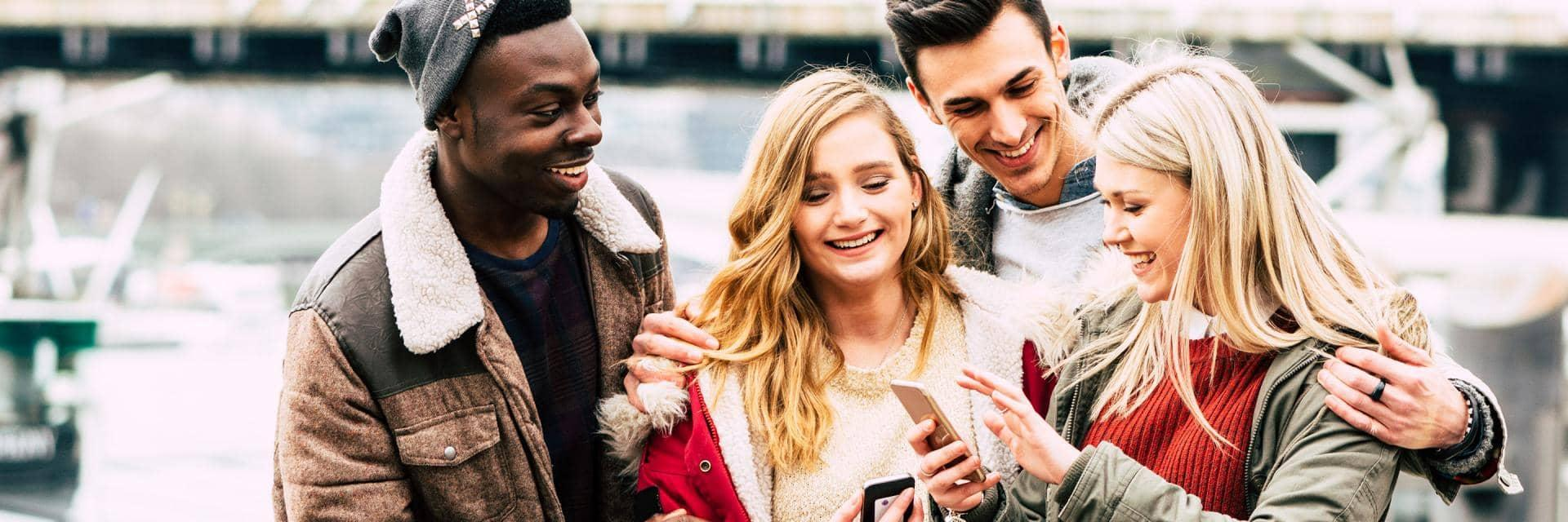 A group of young people wearing winter clothes laugh as they look at something on a mobile phone