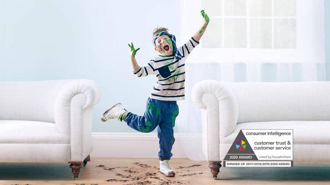A young boy with muddy feet and covered in green paint, dances between two white sofas
