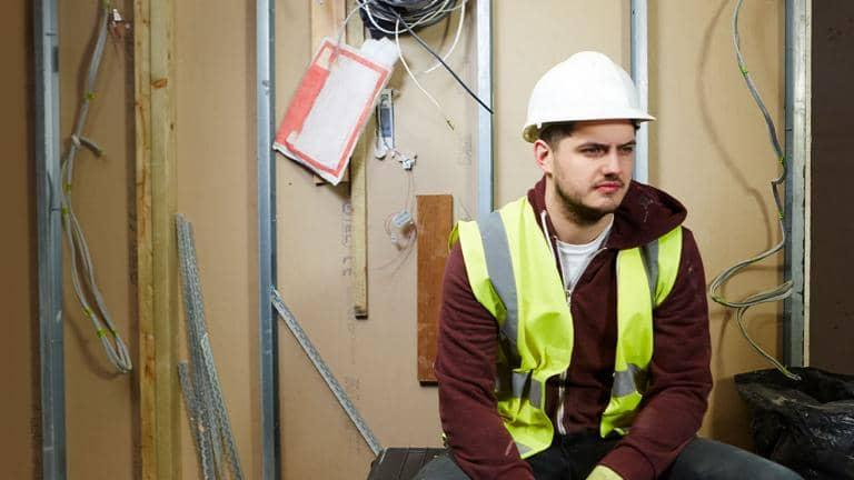 A construction worker in a hard hat and hi-vis vest sitting indoors on a building site