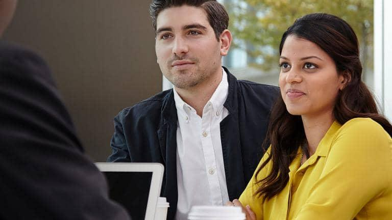 A man and a woman listening to someone at a table with a laptop inbetween