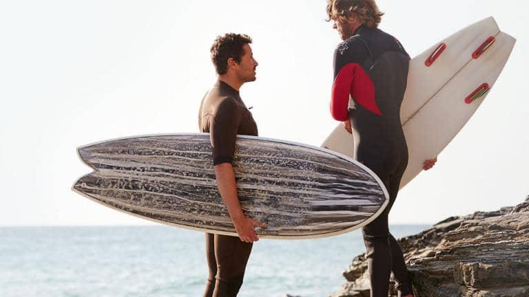 Two standing male surfers in wet suits with surfboards under their arms