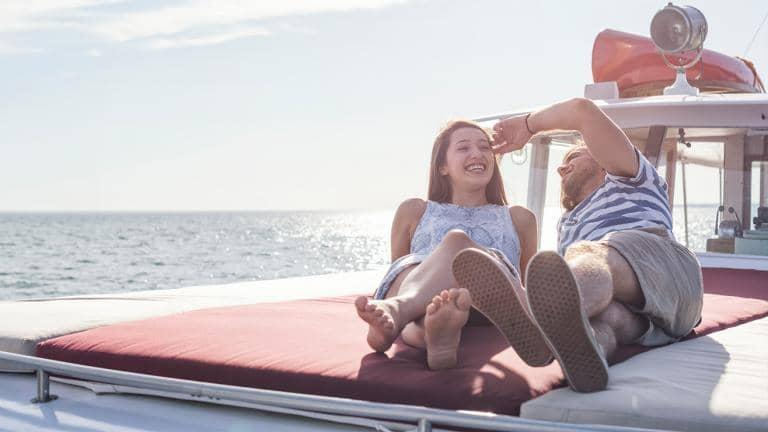 A couple lounging on the front of a boat at sea