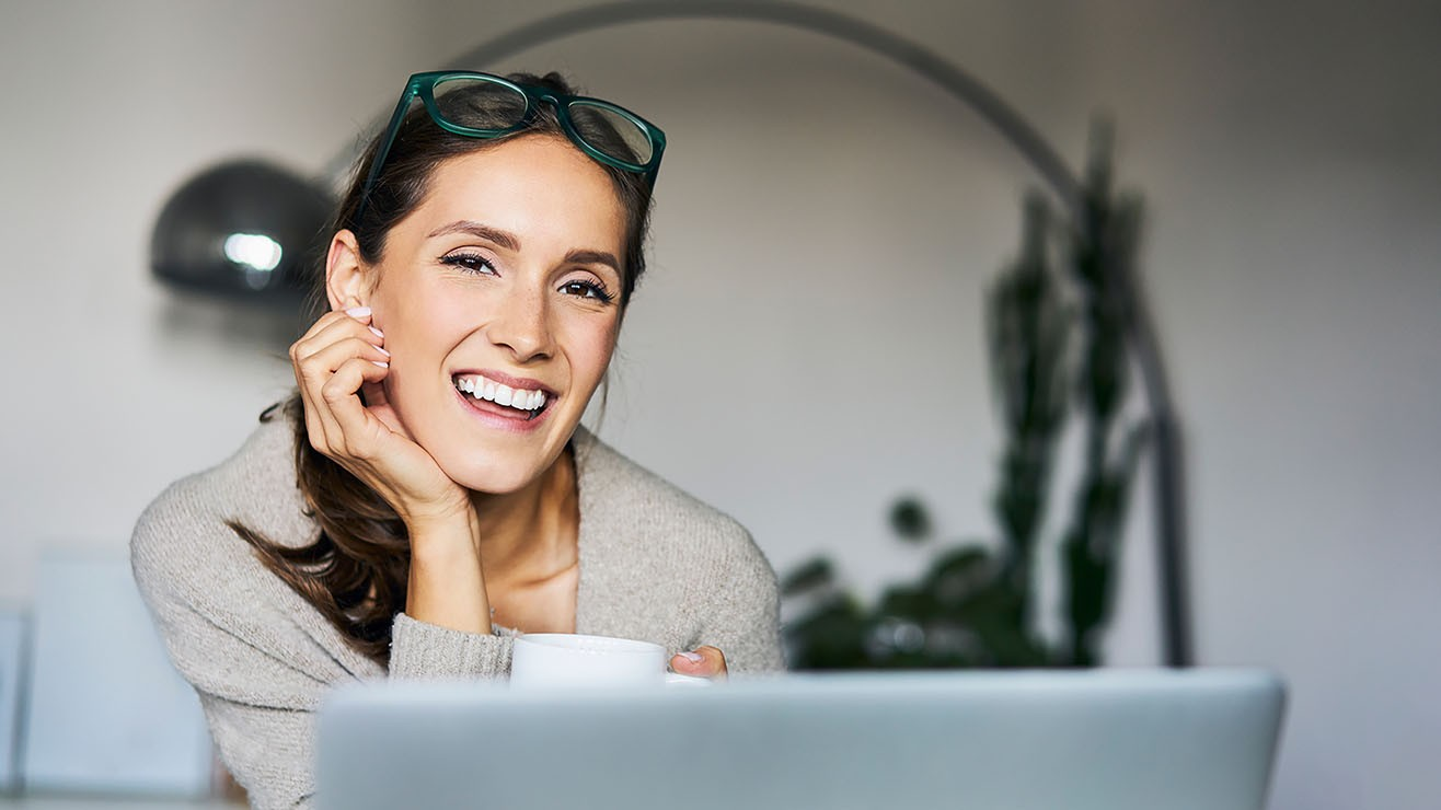 woman sitting in front of laptop, smiling, with glasses on top of her head holding a mug