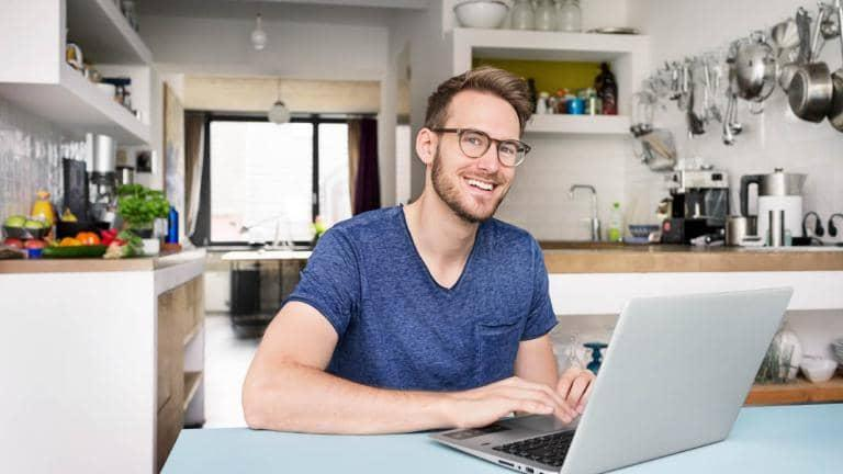 A man sitting behind a laptop in his kitchen smiles at the camera