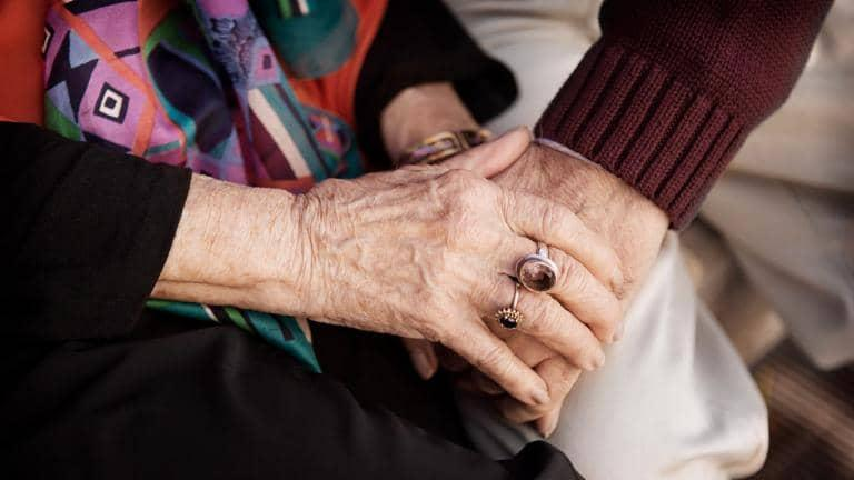 A person holds the hand of an elderly woman who is wearing rings on her fingers