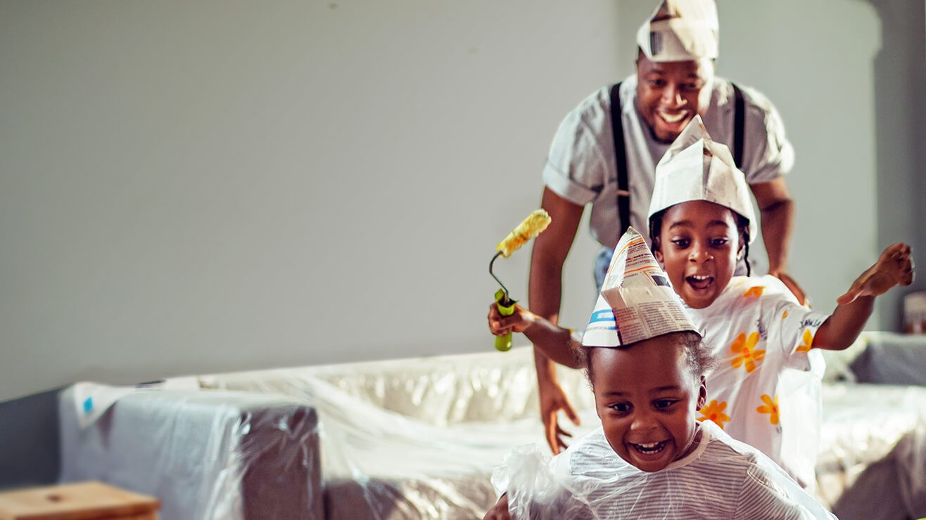 Father and his young children playing and decorating home