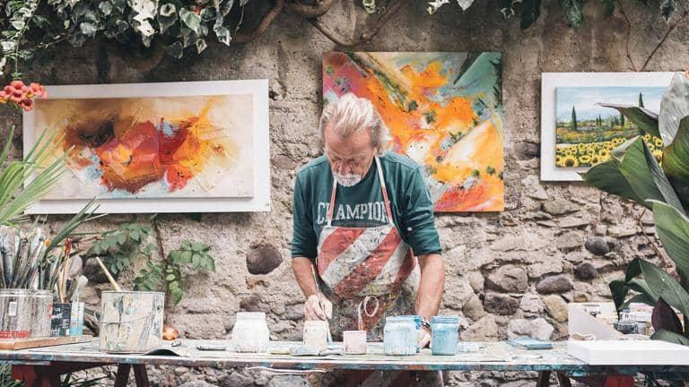 A man wearing an apron paints a canvas on a table covered in pots and brushes