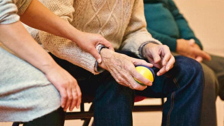 A woman touching the wrist of an elderly person who is holding a ball