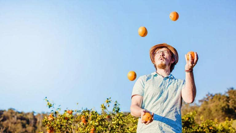 A man wearing a sunhat juggles oranges in an orange grove