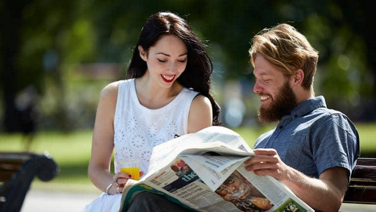 A man and a woman sitting on a park bench look at a newspaper