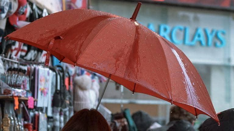 A person holding up an umbrella in the rain in front of a Barclays branch