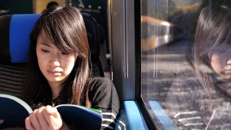 A woman sitting on a train reads a book