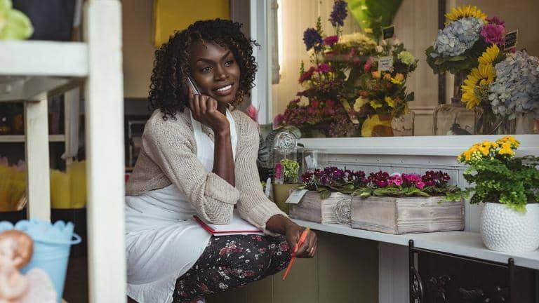 A florist wearing an apron takes a call on her mobile