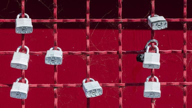 Padlocks locked onto a red-painted fence