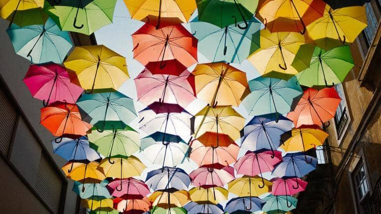 A canopy of colourful umbrellas hanging above a street