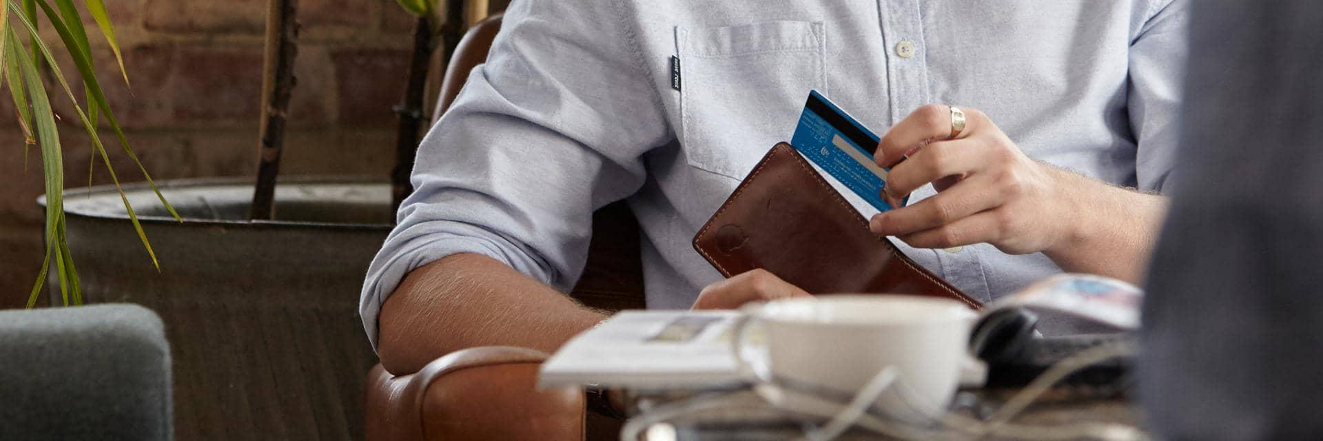 Close up of a man taking a blue bank card from a wallet