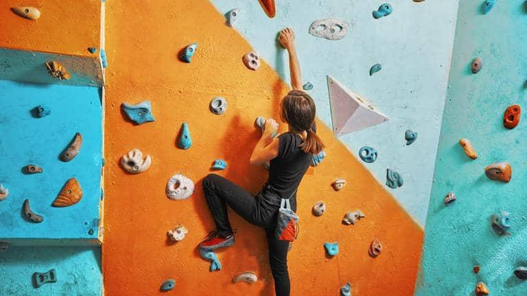A woman climbs up an indoor climbing wall
