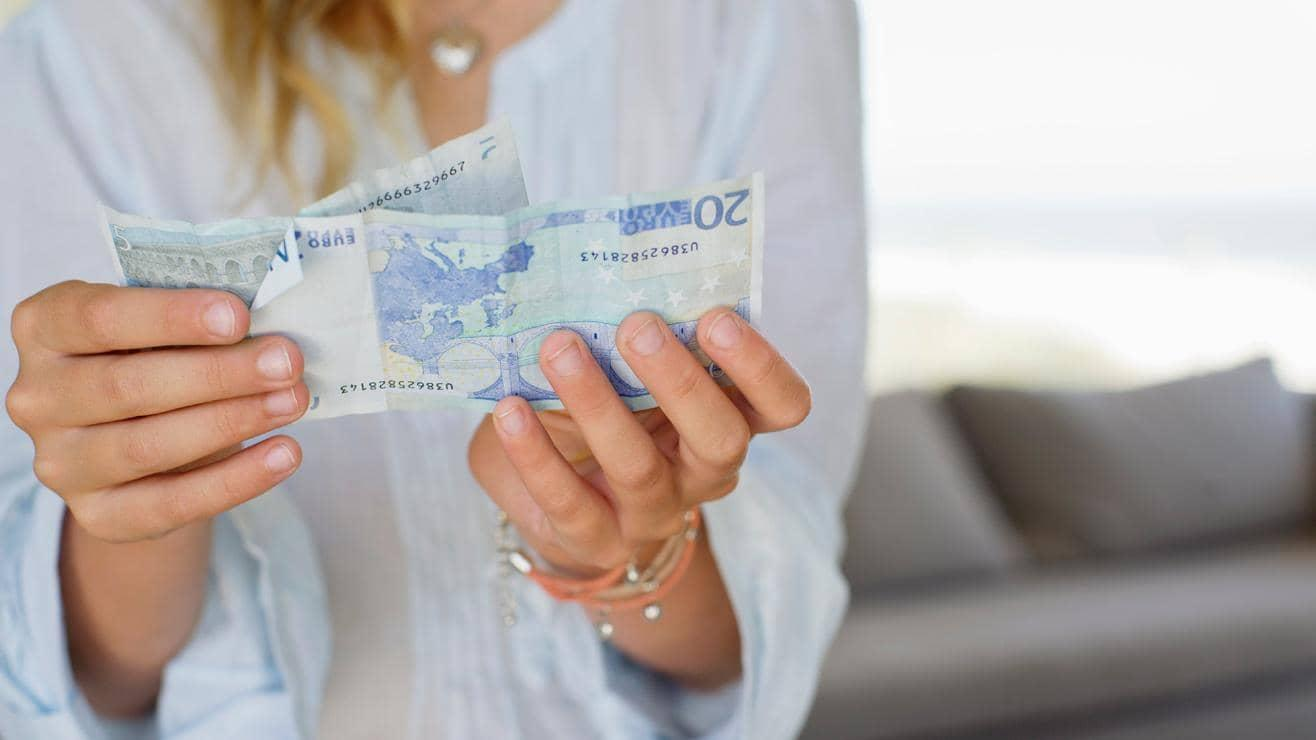 A woman holding two Euro notes