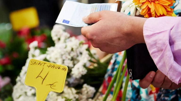 Hands holding a euro bank note and a purse at a flower stall