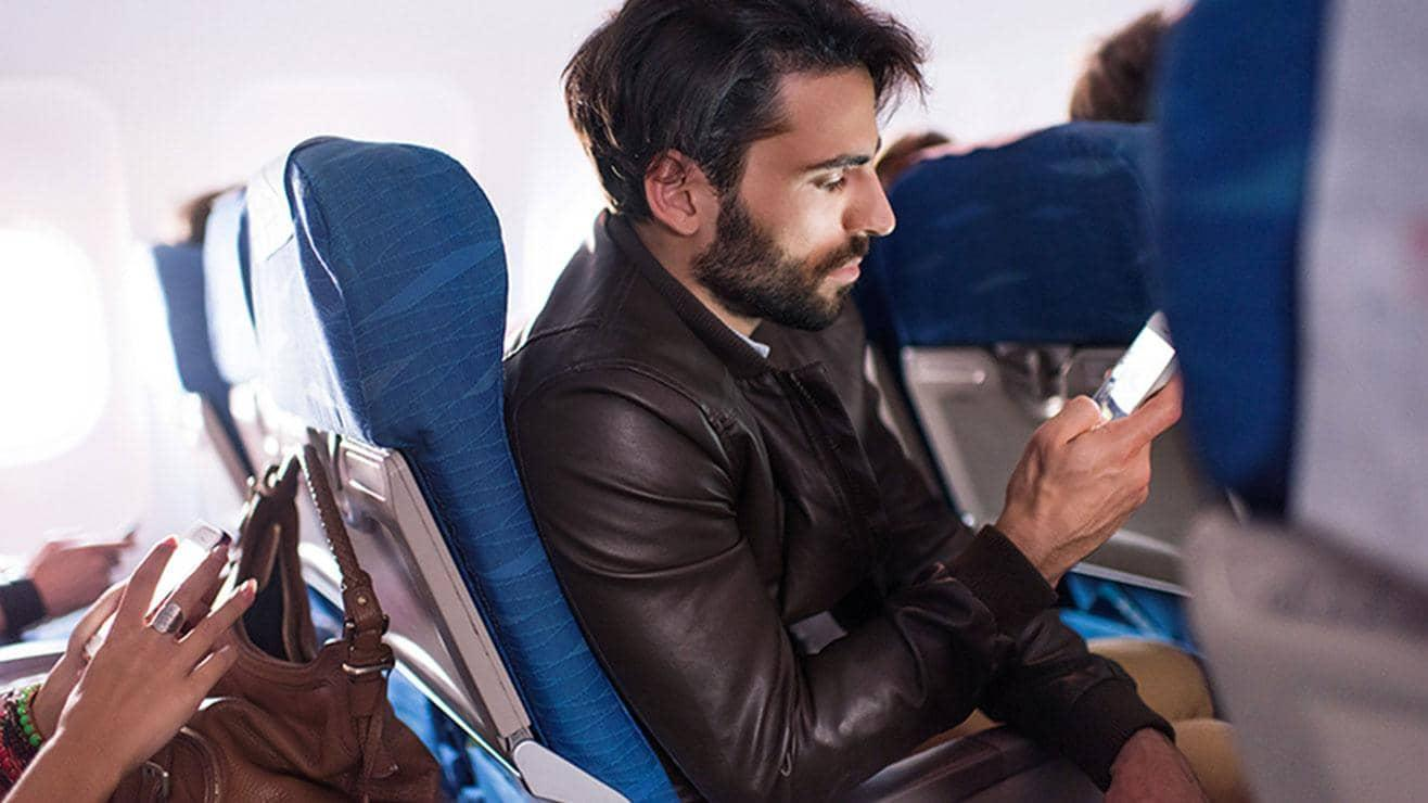 A man sitting on a plane looks at his phone