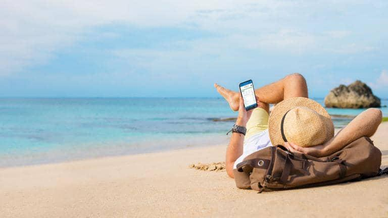 Person laying on beach on top of their bag looking at their phone