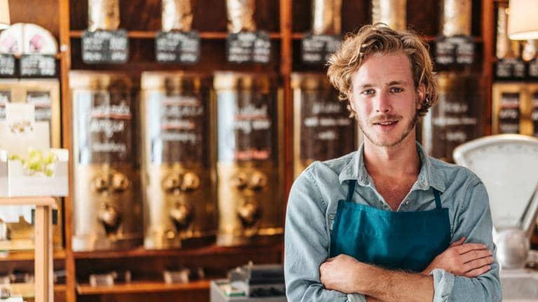 A young man wearing a blue apron stands with his arms crossed in a café