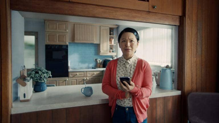 A woman standing in her kitchen holding her mobile phone