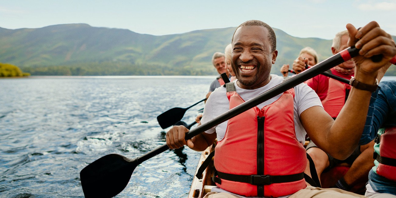 Happy rowers in boat on a lake surrounded by lush green hills